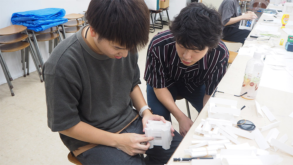アイディアを見せ合う学生画像